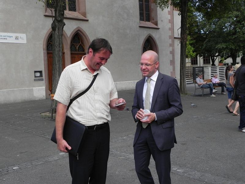 """Baschi Dürr verteilt auf dem Claraplatz Bierdeckel zur Veranstaltungsreihe """"Auf ein Bier mit Baschi Dürr"""""""